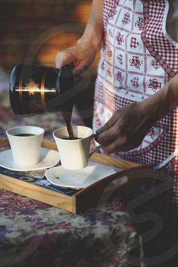 Woman in apron pouring coffee in cups photo