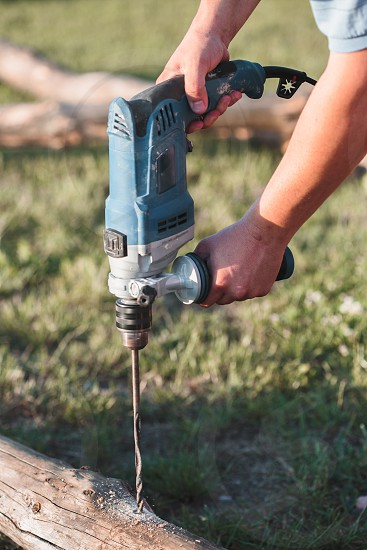 Man drilling hole in timber while working in garden photo