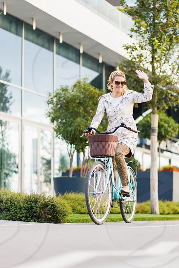 Young happy woman riding a bicycle in the city photo