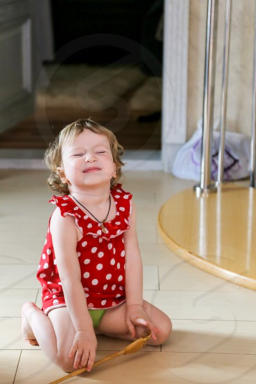 A little girl in a red dress sits on the floor screwing up her eyes photo
