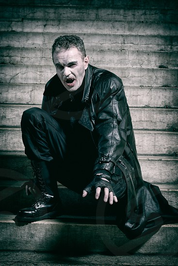 man in black leather coat black leather gloves and black leather boots kneeling on grey concrete staircase with cracks at daytime photo