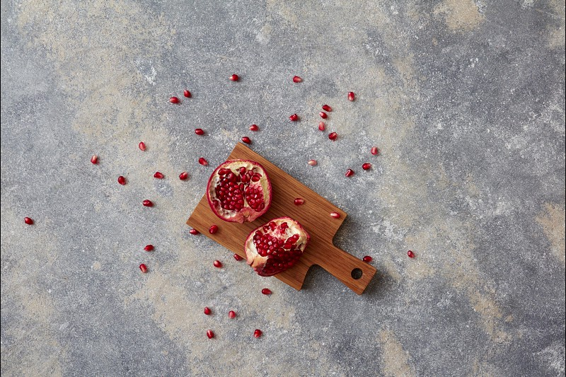 Ripe juicy red garnet and moving fruit grains on a wooden board on a gray concrete background. Stop motion animation. Flat lay. photo