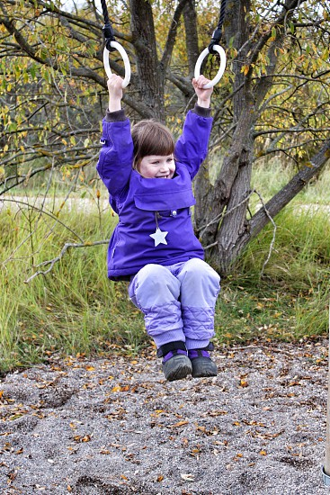 girl in winter apparel on swing rings photo