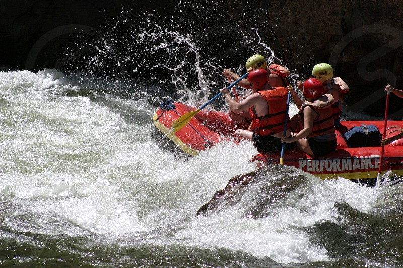 four person riding on inflatable boat on wavy body of water during daytime photo