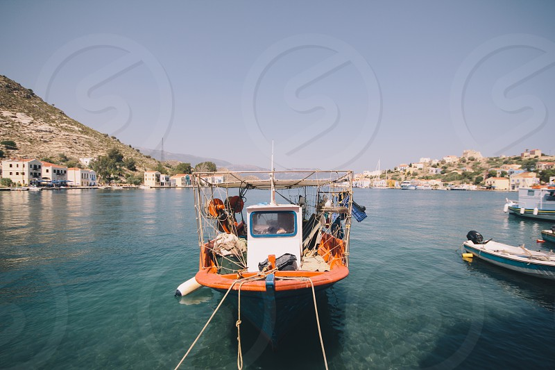white and orange boat on body of water photo