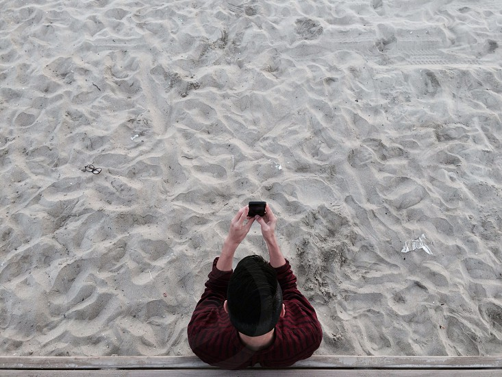 person at a sandy beach taking a picture photo