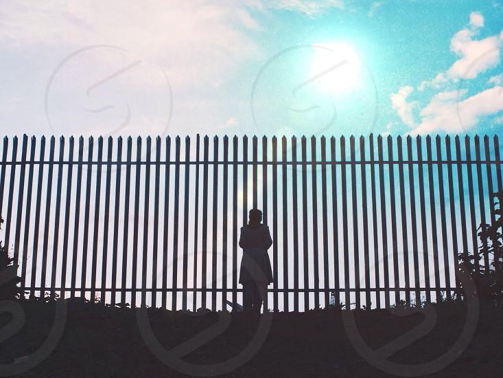 Silhouette. Bars. Fence. Sun. Sunset. Blue sky.  photo