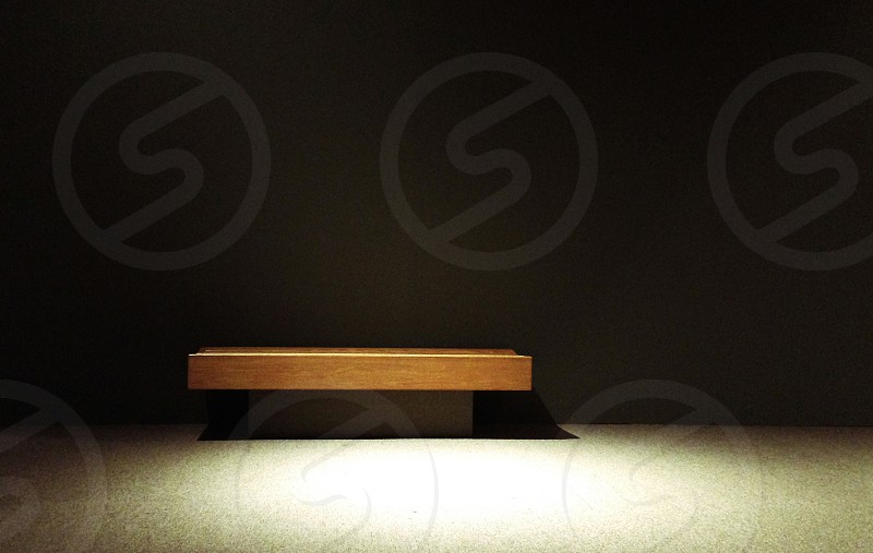 A small wooden bench is in an interior space with a dark background and bright contrasting light photo