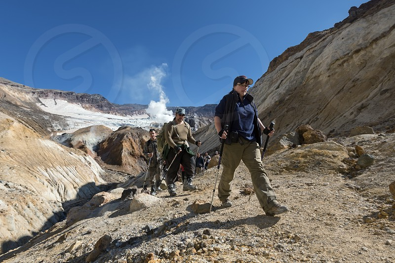 KAMCHATKA RUSSIA - SEPTEMBER 11 2013: Group of tourists climbing the narrow canyon in the crater Mutnovsky Volcano - picturesque active volcano on Kamchatka on a sunny day. Russia Far East. photo