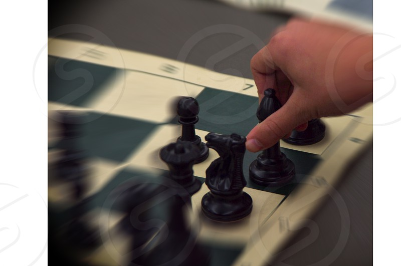 Hand moving chess piece on board during competition photo