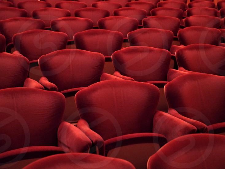 Red rows of cinema theater velvet seats photo