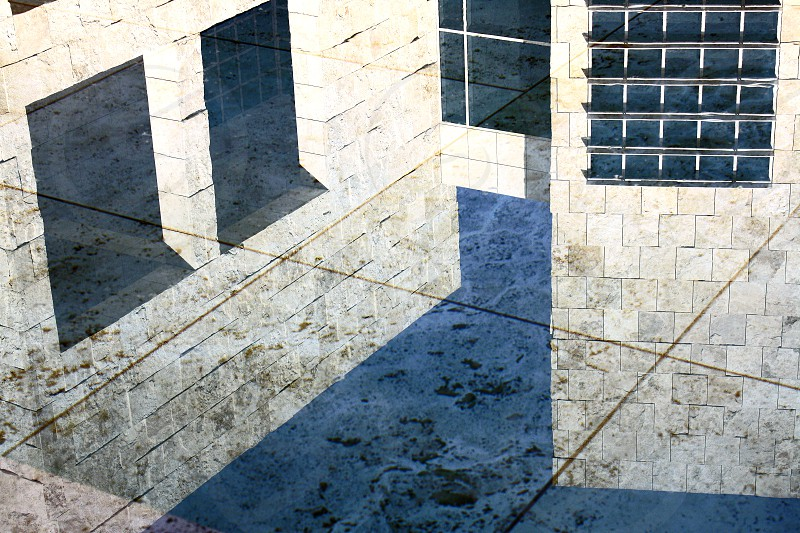The tops of three marble museum buildings are reflected in the water of a fountain. photo
