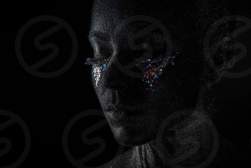 Conceptual art Portrait of Beautiful Woman in Black makeup with Sparkles on a Face isolated on a dark background photo