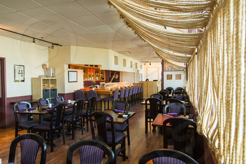 black chairs and tables inside the restaurant with brown tasseled window curtain photo