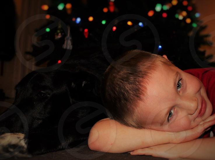 boy wearing a red cotton tee head down on his arm while a black labrador retriever lies next to him photo
