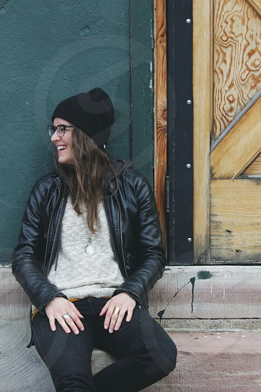 woman in black beanie wearing black leather jacket sitting on gray concrete pavement photo