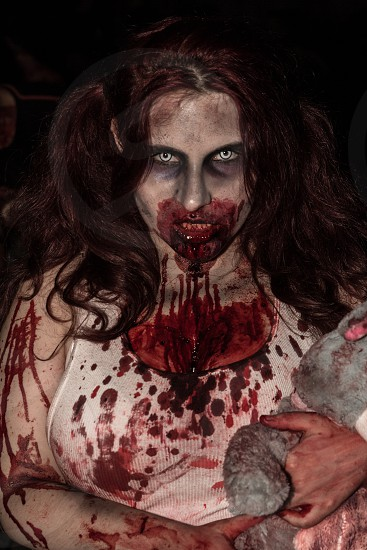 zombie woman in white tank top holding a grey plush toy full of red blood stains dripping from her mouth photo