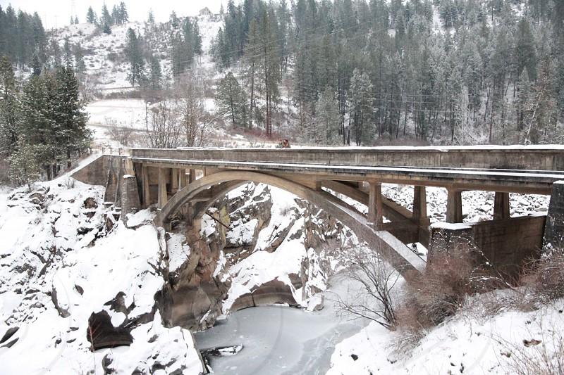brown and black metal bridge beside snow field photo