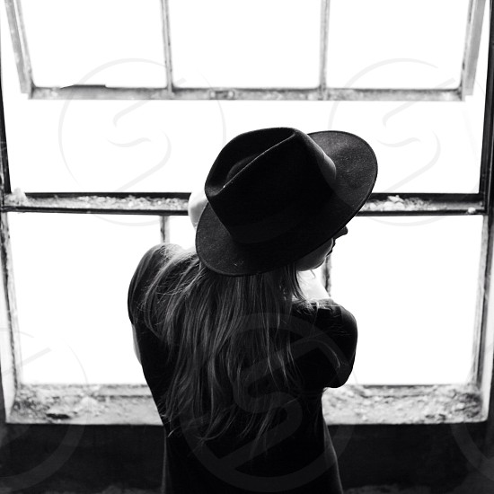 Woman with long blonde hair wearing a fedora hat in front of a window photo