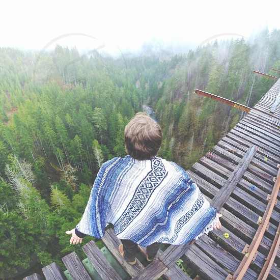 woman with blue and white poncho in a wooden bridge overlooking a green forest photo