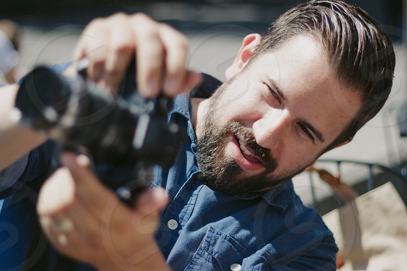man in blue button down shirt holding black dslr camera photo