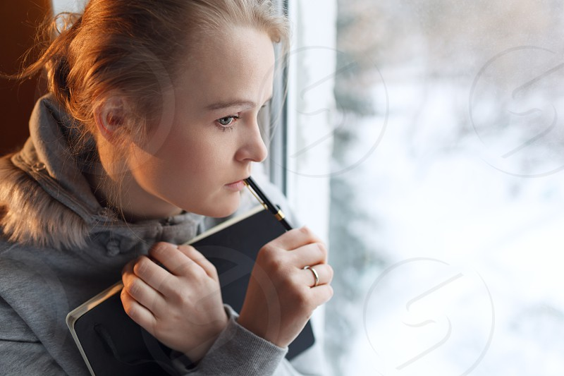 Young girl is dreaming by the window with notebook and pen photo