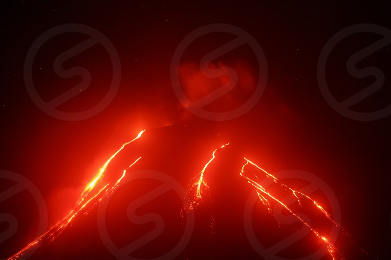 Volcanic landscape of Kamchatka Peninsula: night view of eruption Klyuchevskoy Volcano current lava flows on slope of volcano. Eurasia Russia Far East Kamchatka Klyuchevskaya Group of Volcanoes. photo