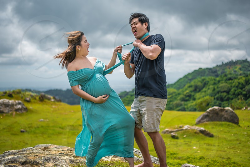 woman binds man's neck by her dress during daytime photo
