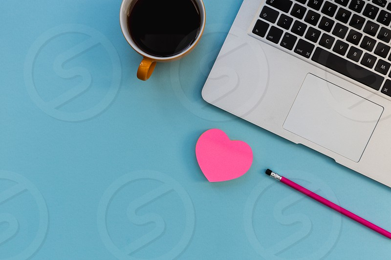 Minimal laptop computer love pink heart on bright blue background photo