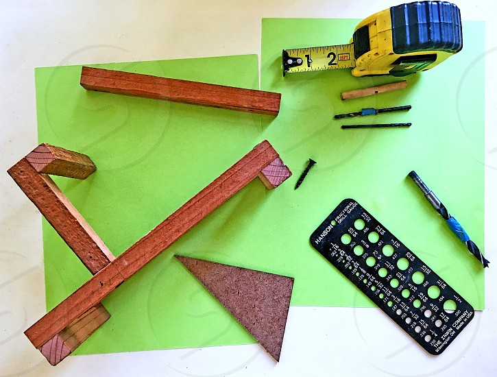 Aerial view of wooden bars tape measure angles and drill bit for a school physics project. photo
