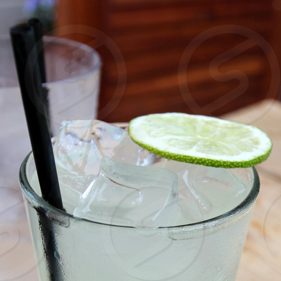 Limeade with lime slice in glass with straw and ice photo