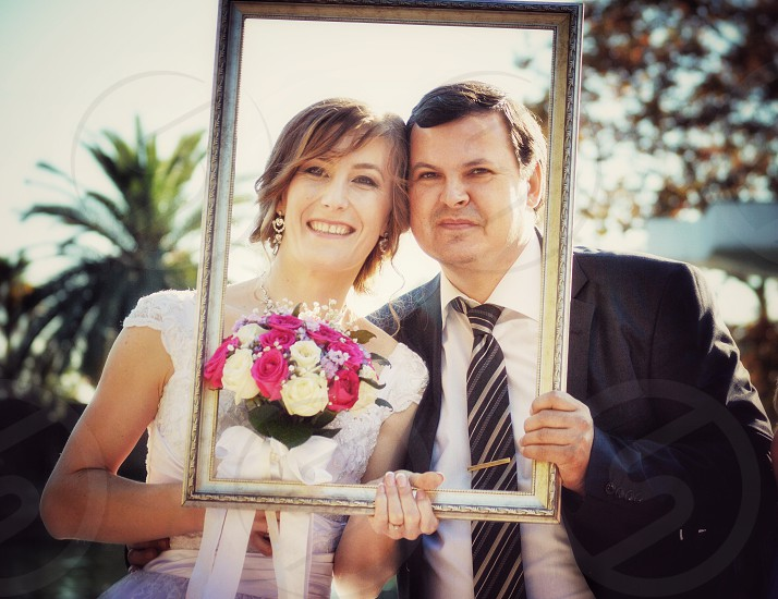 wedding couple posing inside a brown wooden rectangular photo frame for photo photo