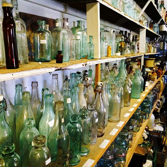 close photo of row of glass bottles on wooden shelf photo