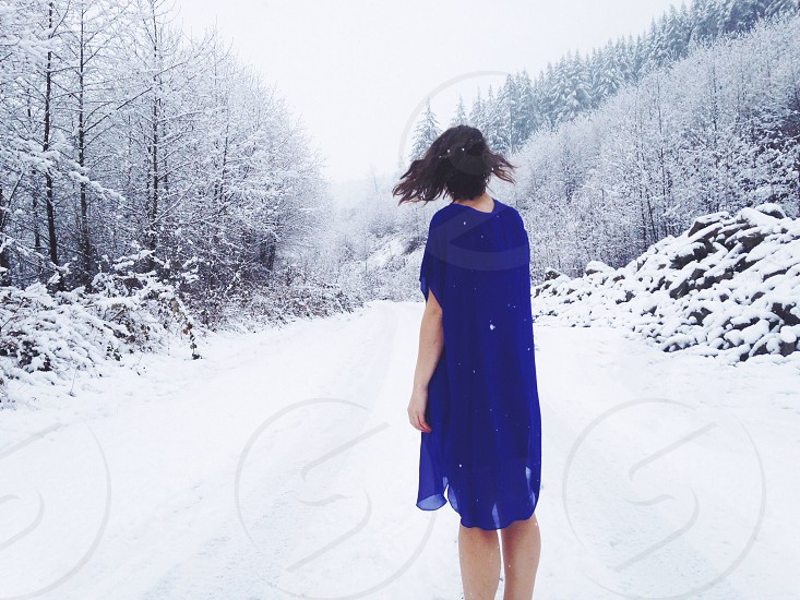 woman wearing blue dress standing on a snow covered road photo