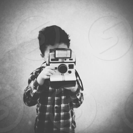 boy holding camera taking photo photo