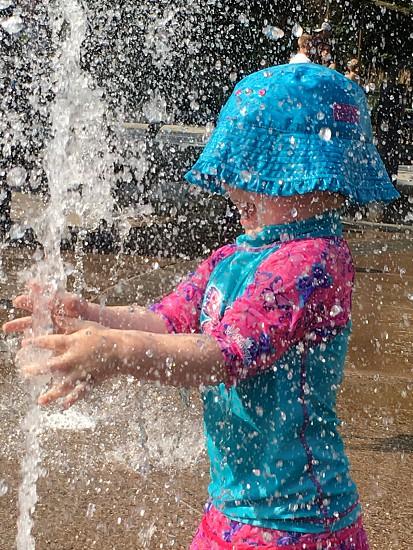 Toddler girl enjoying the fountain spray photo