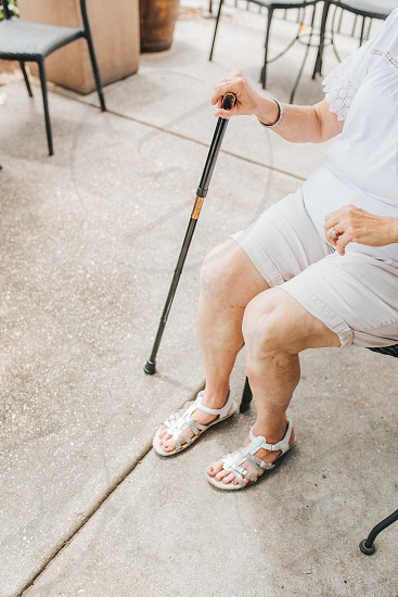 Elderly woman who just had knee surgery sitting down with her cane photo