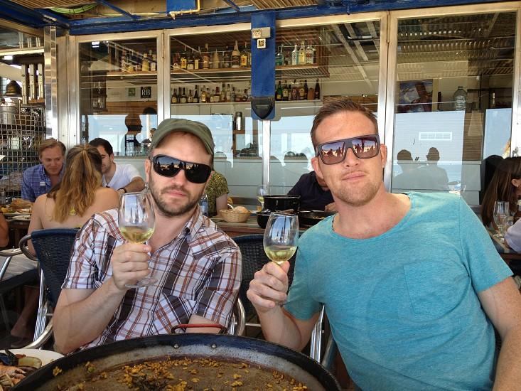 2 men holding tulip wine glass photo