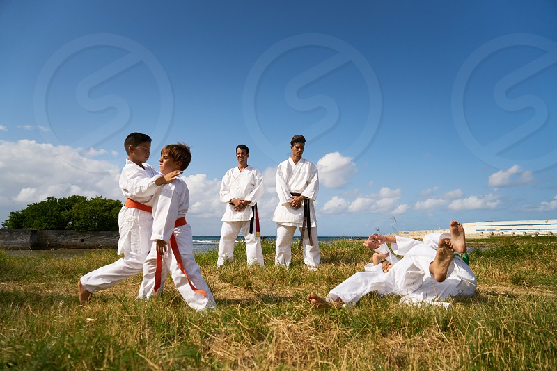 Combat and extreme sports hispanic men and children exercising in karate and traditional martial arts. Simulation of fight on the beach photo