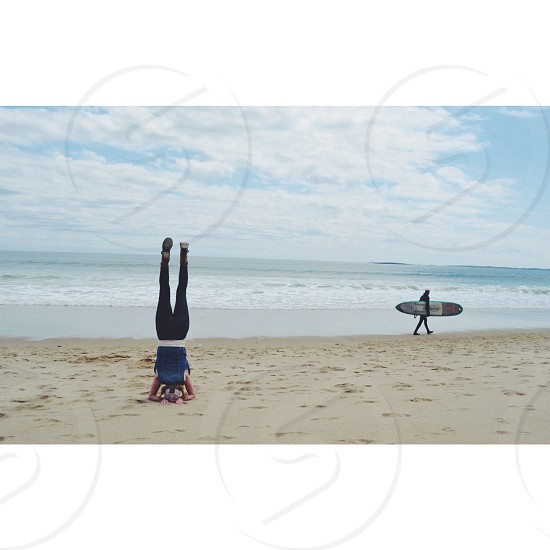 Beach yoga with passing surfer. Southern Maine coast. photo