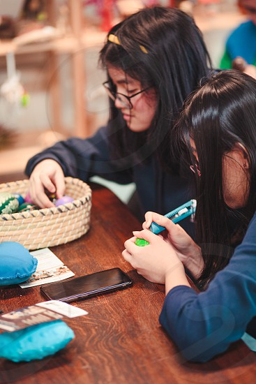 Women decorating the Easter eggs by scratching patterns on dyed eggs. Traditional Easter time spring time new beginnings. Candid people real moments authentic situations photo