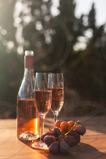two champagne flutes filled with rose wine on a table next to the bottle and purple table grapes surrounded by trees under the sun photo