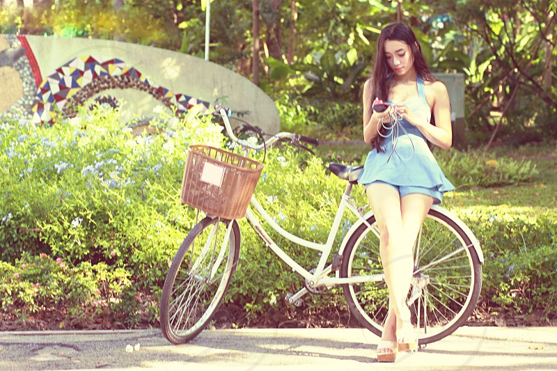 Portrait of Asian woman stand near bicycle and play smartphone in garden scene  photo