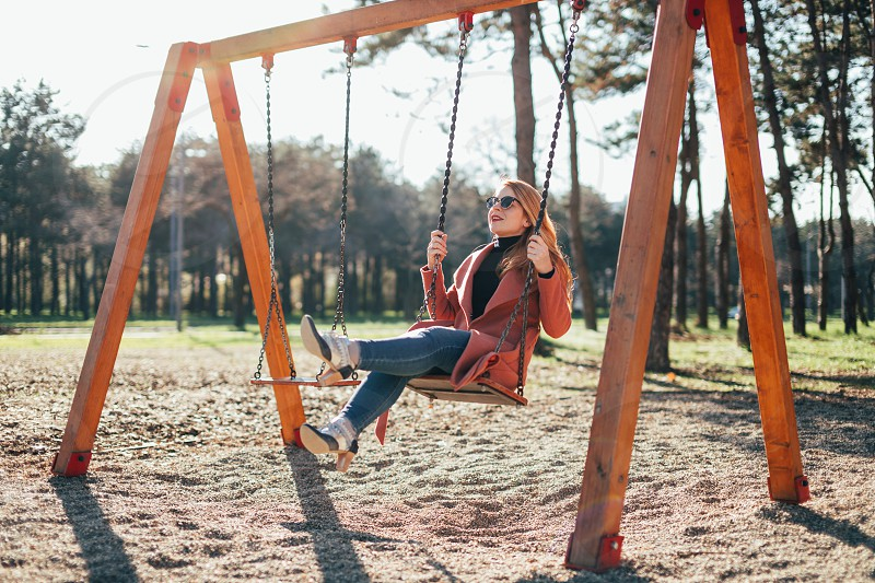 Young happy woman having fun on the swing in the playground photo