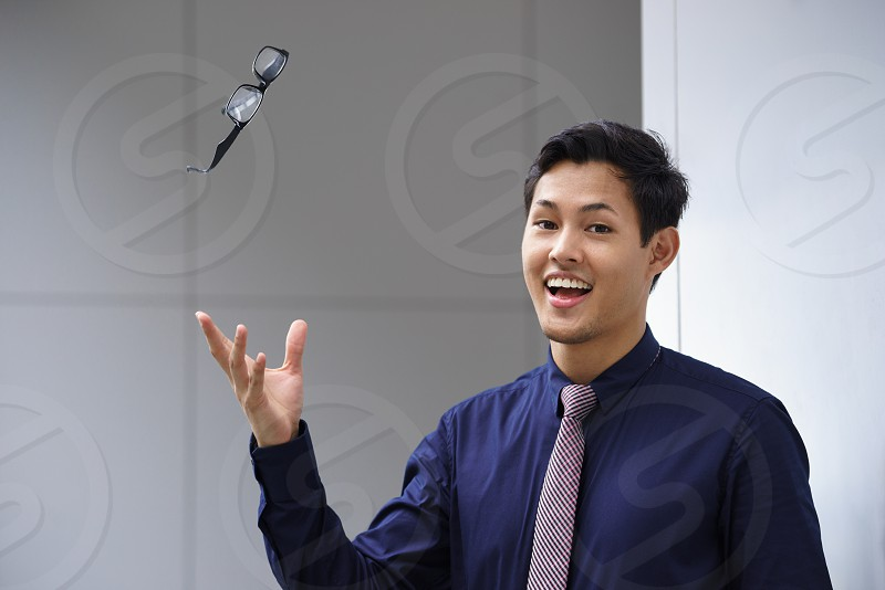 man glasses eyeglasses happy throw throwing away smile smiling asian chinese business businessman corporate suit tie hand one person people male adult eyesight cheerful  photo