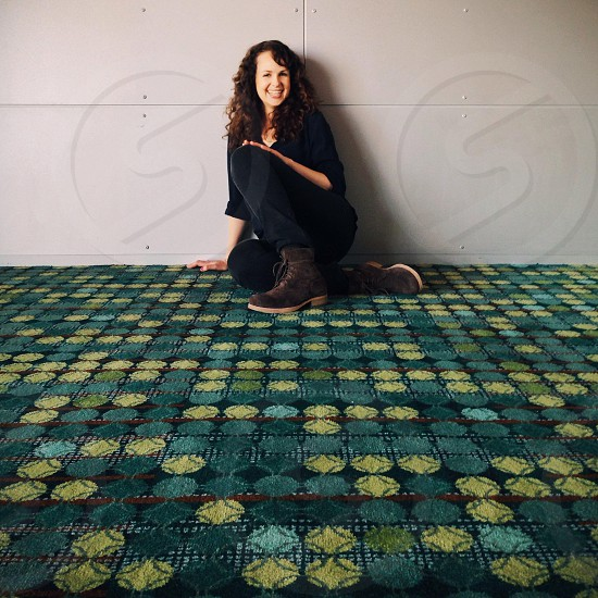 woman sitting on the floor smiling photo