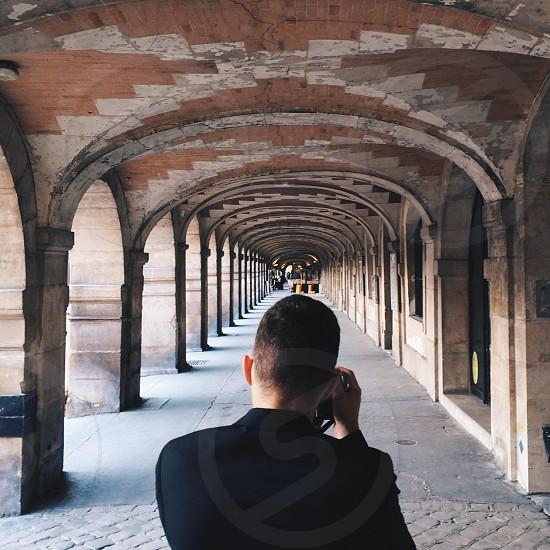 man taking picture on hallway photo