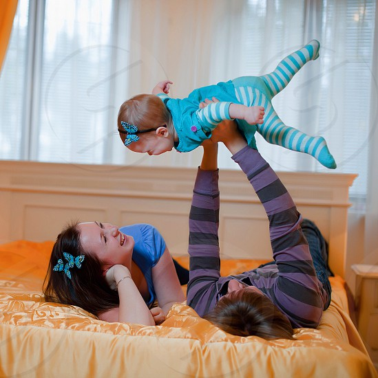 man lying on bed lifting baby on air beside lying woman photo