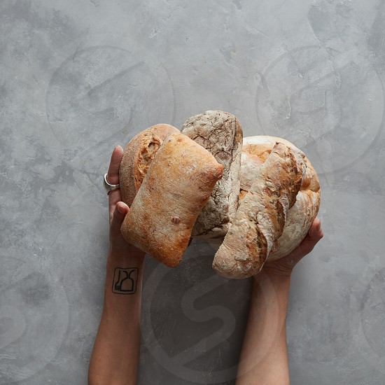 Lots of different bread sorts in the hands of a baker on a gray background Baking and cooking concept background. photo