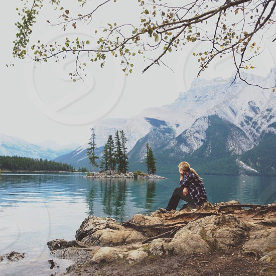 woman in blue and white checked shirt sitting on rock near lake photo